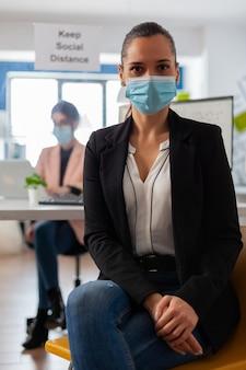 Ciérrese encima del retrato del empleado de la empresa en el espacio de trabajo con la mascarilla como precaución de seguridad durante la pandemia global con el coronavirus mirando a la cámara.