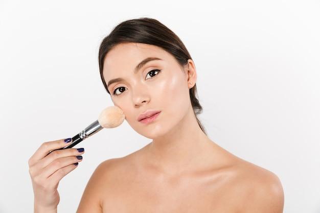 Ciérrese encima del retrato del estudio de la mujer asiática hermosa con la piel suave que aplica maquillaje con el cepillo aislado sobre blanco