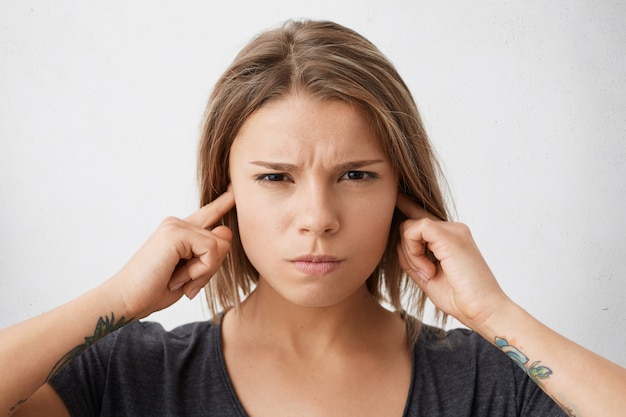 Ciérrese encima del retrato de la hembra joven enojada molesta de la raza mixta que tapa sus oídos para evitar el ruido fuerte de los vecinos en el apartamento de arriba, que tiene la mirada irritada. reacciones y emociones humanas negativas