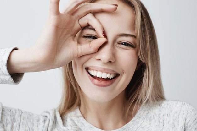 Ciérrese encima del retrato de la hembra rubia caucásica alegre hermosa que sonríe, demostrando los dientes blancos, mirando con los dedos en gesto aceptable. expresiones faciales, emociones y lenguaje corporal.