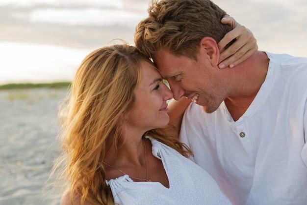 Ciérrese encima del retrato de la hermosa pareja europea abrazándose contra la puesta de sol.