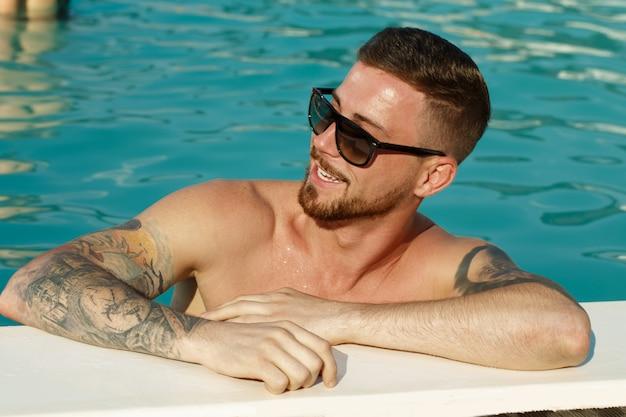 Ciérrese encima del retrato de un hombre barbudo hermoso en gafas de sol que sonríe mirando lejos