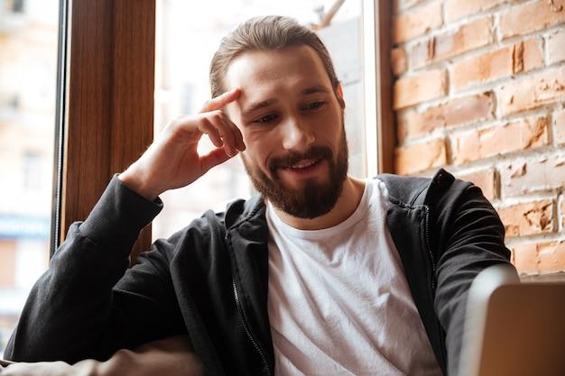 Ciérrese encima del retrato del hombre barbudo que usa la computadora portátil en café