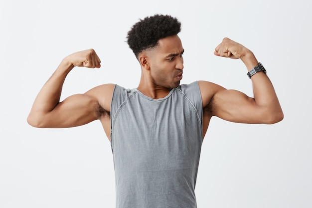 Ciérrese encima del retrato del hombre deportivo joven de piel oscura con el peinado afro en la camisa gris que muestra sus músculos, mirándolo con la expresión concentrada de la cara. salud y belleza