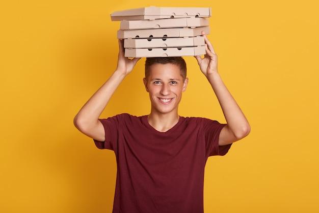Ciérrese encima del retrato del hombre de entrega alegre joven con la camiseta roja que se coloca, sosteniendo la pila de cajas de pizza de cartón en la pared gris.