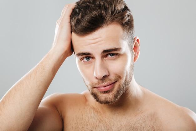 Ciérrese encima del retrato de un hombre hermoso que se peina