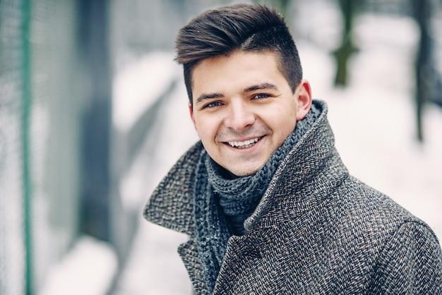 Ciérrese encima del retrato del hombre joven sonriente hermoso en un abrigo caliente que camina dowm la calle