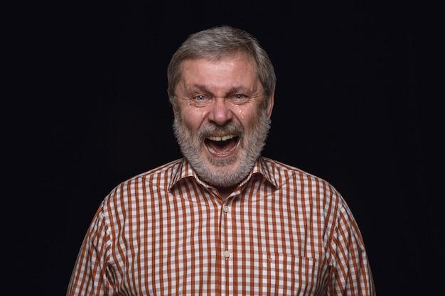 Ciérrese encima del retrato del hombre mayor aislado en la pared negra. emociones reales del modelo masculino. llorando a través de la risa y la sonrisa. expresión facial, concepto de emociones humanas.