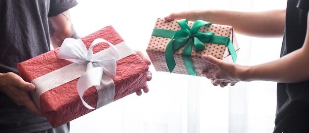 Ciérrese encima del retrato del hombre y de la mujer que intercambian regalos diferentes aislados en blanco. presenta compartir entre personas