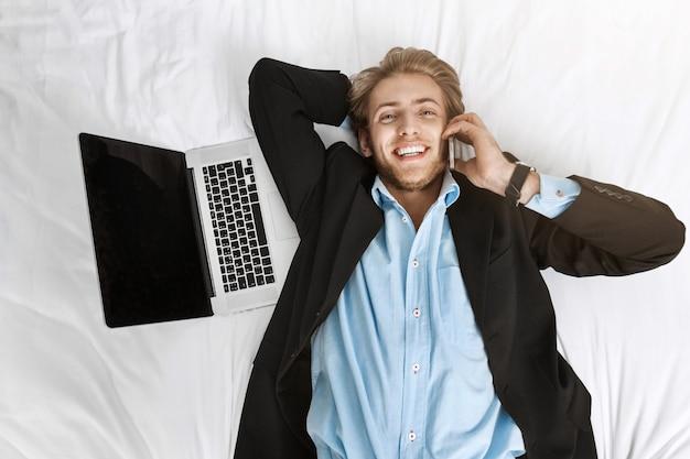 Ciérrese encima del retrato del hombre de negocios joven apuesto que miente en cama con la computadora portátil, hablando en el teléfono con la expresión feliz.