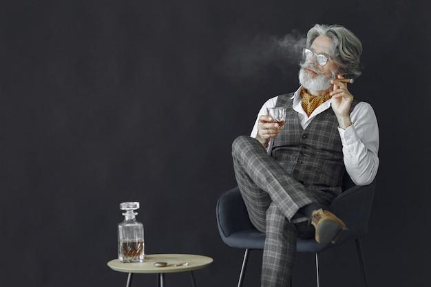 Ciérrese encima del retrato del hombre pasado de moda sonriente. abuelo con un puro y whisky.