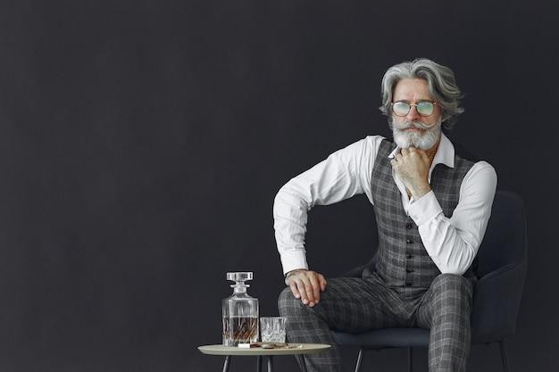 Ciérrese encima del retrato del hombre pasado de moda sonriente. gentelman sentado en una silla. abuelo con un vaso de whisky.