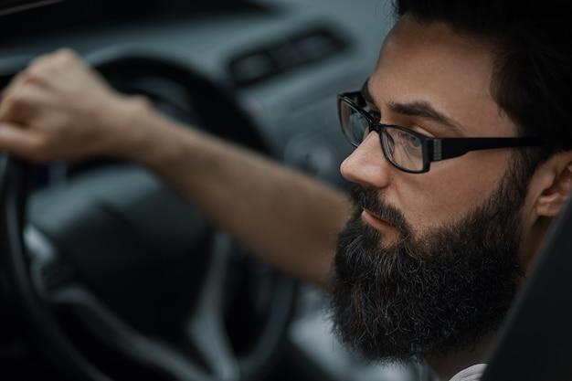 Ciérrese encima del retrato, hombre serio que conduce un coche