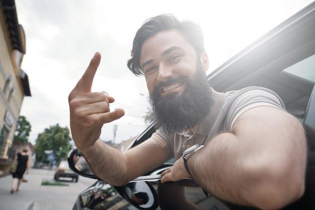 Ciérrese encima del retrato lateral del hombre feliz que conduce el coche