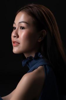 Ciérrese encima del retrato lateral de la mujer asiática hermosa con la sonrisa larga del pelo. joven modelo asiático en estudio.
