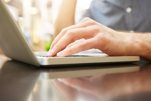 Ciérrese encima del retrato de la mano masculina que mecanografía en la computadora portátil en el café exterior