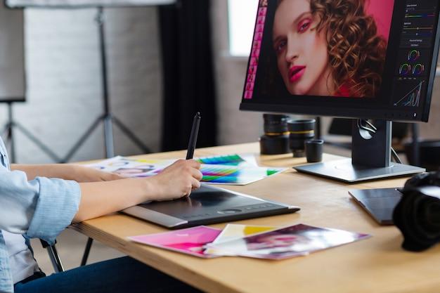 Ciérrese encima del retrato de las manos del diseñador gráfico que retocan imágenes usando la tableta gráfica del dibujo en programa especial.