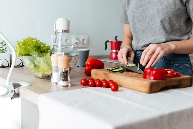Ciérrese encima del retrato de las manos femeninas que cortan verduras