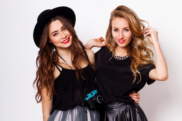 Ciérrese encima del retrato de la moda de dos mujeres elegantes elegantes que llevan una falda de cuero y un sombrero negro, sosteniendo la cámara retra. posando contra el fondo blanco.