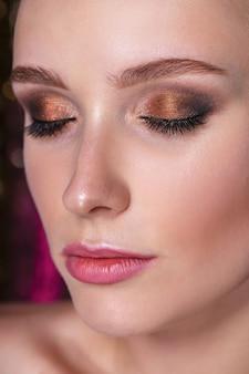 Ciérrese encima del retrato de la modelo joven atractiva con maquillaje brillante