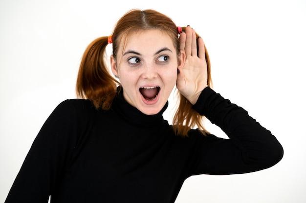Ciérrese encima del retrato de la muchacha adolescente bastante pelirroja que lleva a cabo una mano a su oído escuchando un secreto.