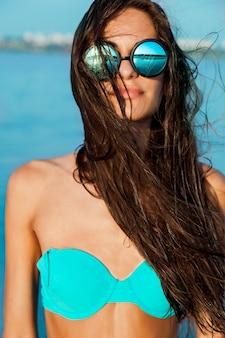 Ciérrese encima del retrato de la muchacha atractiva hermosa elegante en vidrios y con el pelo mojado en una playa soleada con agua azul. toma el sol y disfruta del resto.