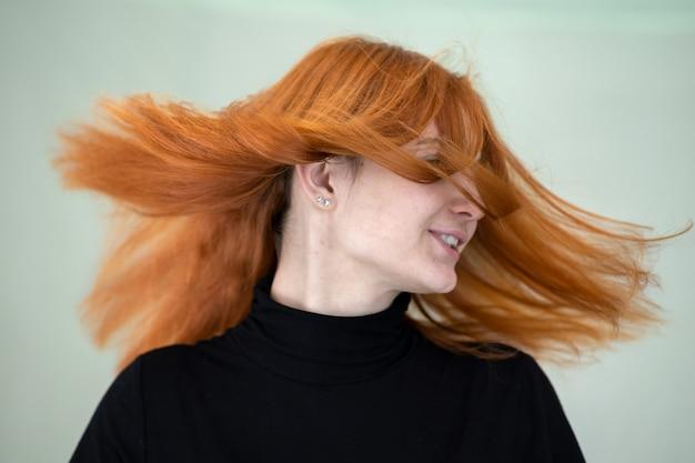 Ciérrese encima del retrato de la muchacha bonita del pelirrojo con el pelo ondulado largo que sopla en el viento