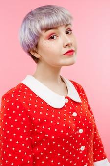 Ciérrese encima del retrato de la muchacha dollish hermosa con el pelo violeta claro corto que lleva el vestido rojo sobre la pared rosada