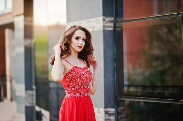 Ciérrese encima del retrato de la muchacha de moda en el vestido de noche rojo que plantea la ventana del espejo del fondo del edificio moderno
