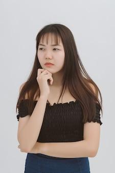 Ciérrese encima del retrato de la muchacha pensativa confiada hermosa asiática que se coloca sobre gris la mujer asiática que lleva a cabo la mano cerca de su cara parece seria.