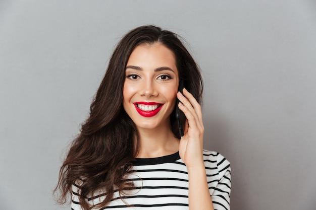 Ciérrese encima del retrato de una muchacha que habla en el teléfono móvil