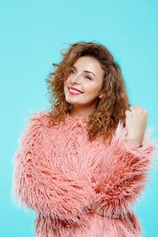 Ciérrese encima del retrato de la muchacha rizada morena hermosa sonriente alegre en abrigo de pieles rosado sobre la pared azul