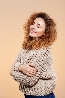 Ciérrese encima del retrato de la muchacha rizada morena hermosa sonriente alegre en suéter hecho punto sobre la pared beige