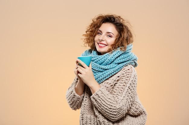 Ciérrese encima del retrato de la muchacha rizada morena sonriente hermosa alegre en suéter hecho punto y el calentador gris que sostiene la taza sobre la pared beige