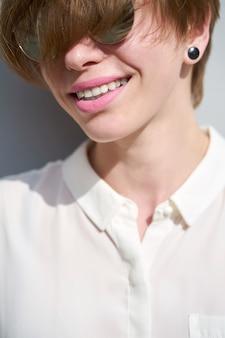 Ciérrese encima del retrato de la muchacha sonriente de la pelirroja caucásica joven con el peinado corto y los labios pintados lápiz labial rosado en gafas de sol