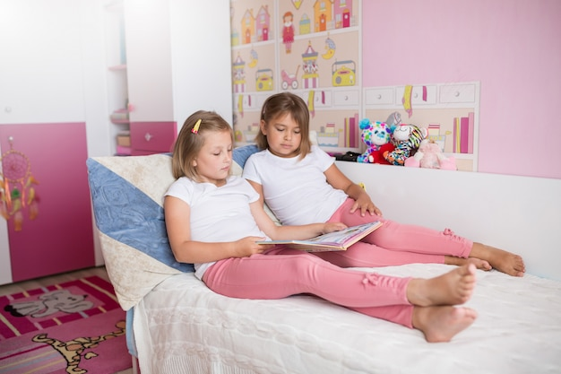 Ciérrese encima del retrato de las muchachas adorables caucásicas que leen el libro juntos en dormitorio acogedor
