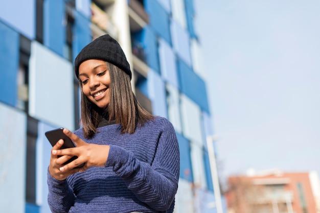 Ciérrese encima del retrato de una mujer africana joven hermosa que usa el teléfono celular al aire libre en la ciudad