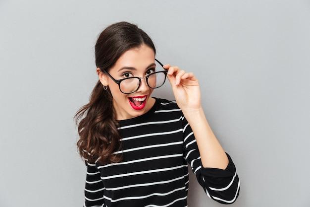 Ciérrese encima del retrato de una mujer alegre en lentes