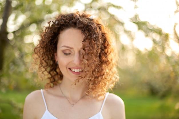 Ciérrese encima del retrato de la mujer atractiva sonriente de los jóvenes con el pelo rizado en parque floreciente verde de la primavera. puras emociones.