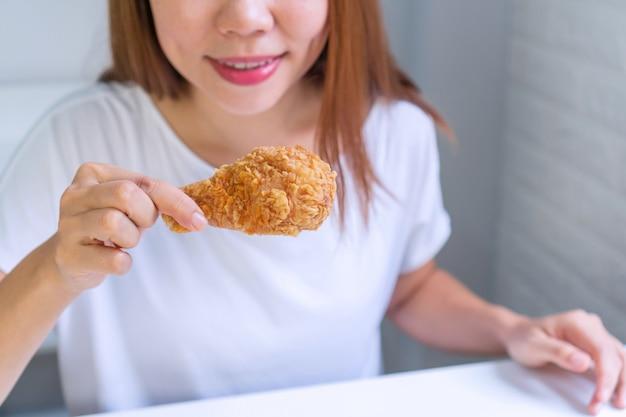 Ciérrese encima del retrato de una mujer bastante asiática satisfecha que come el pollo frito aislado
