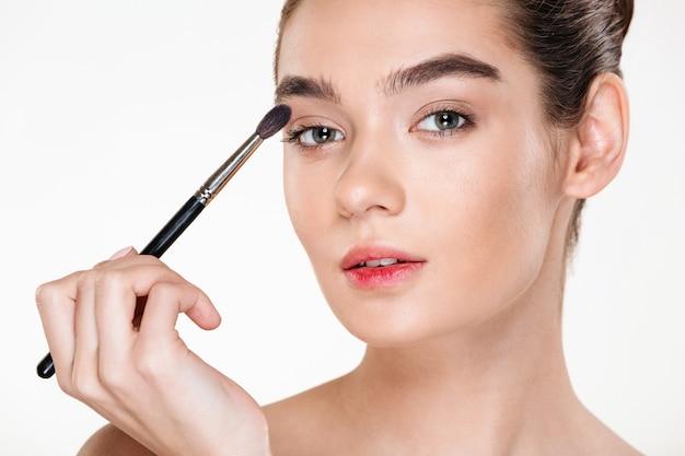 Ciérrese encima del retrato de la mujer bonita apacible con la piel sana que aplica maquillaje pintando los ojos con el cepillo