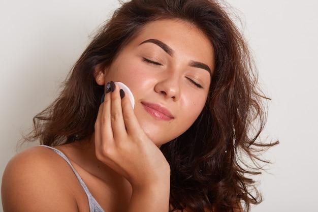 Ciérrese encima del retrato de la mujer caucásica joven que lleva la camiseta gris, sosteniendo la esponja cosmética en mejilla, presentando con los ojos cerrados, cuidando ella misma, quitando los cosméticos, presentando sobre la pared blanca del estudio.