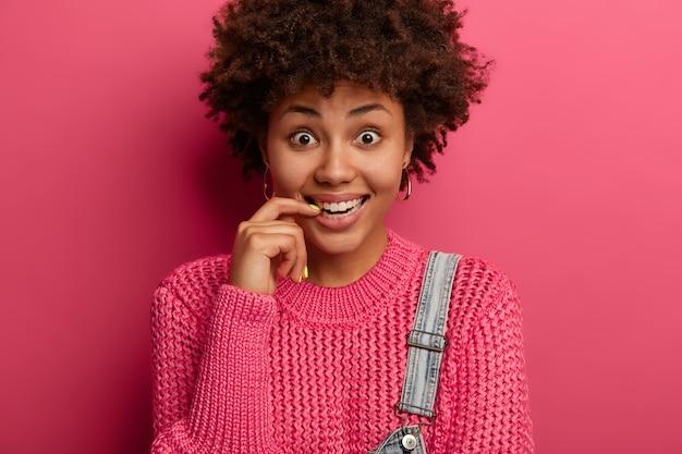 Ciérrese encima del retrato de la mujer curiosa feliz con el pelo afro rizado, sonríe con alegría, viste un jersey de punto de gran tamaño, oye algo hilarante y divertido, aislado sobre una pared rosada.