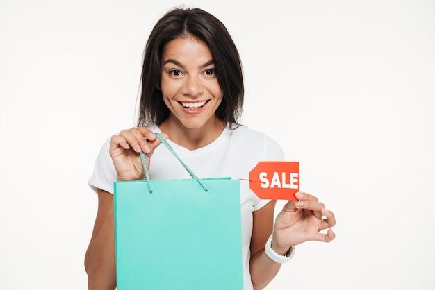 Ciérrese encima del retrato de una mujer feliz que sostiene el bolso de compras