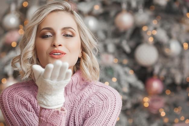 Ciérrese encima del retrato de la mujer hermosa joven en escena de la navidad. niña sonriente con una piel perfecta cerca del árbol de navidad.