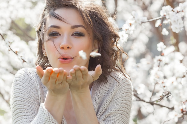 Ciérrese encima del retrato de la mujer hermosa joven en la primavera. chica joven atractiva con flores. maquillaje de primavera modelo.
