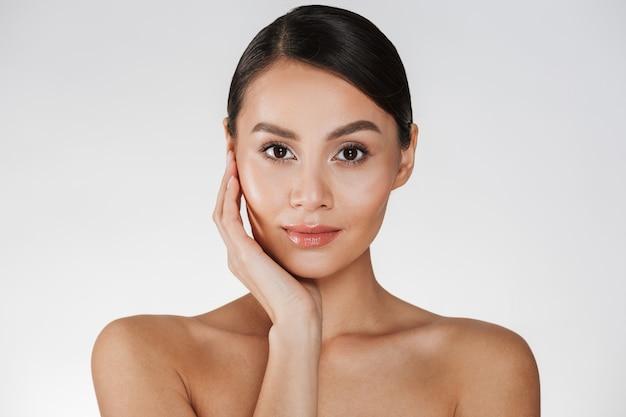 Ciérrese encima del retrato de la mujer hermosa con maquillaje natural que presenta en la cámara con tocar su cara, aislada sobre blanco