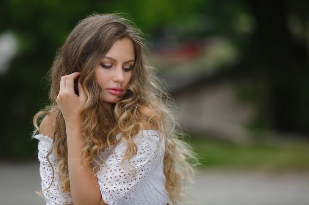 Ciérrese encima del retrato de una mujer hermosa del pelo rizado. hermosa mujer al aire libre en el parque de verano. jovencita en la naturaleza