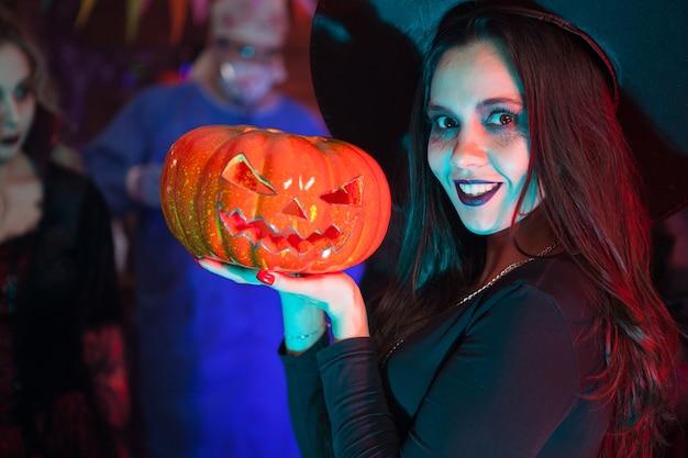 Ciérrese encima del retrato de la mujer hermosa vestida como una bruja para halloween que sostiene una calabaza. evento de halloween.