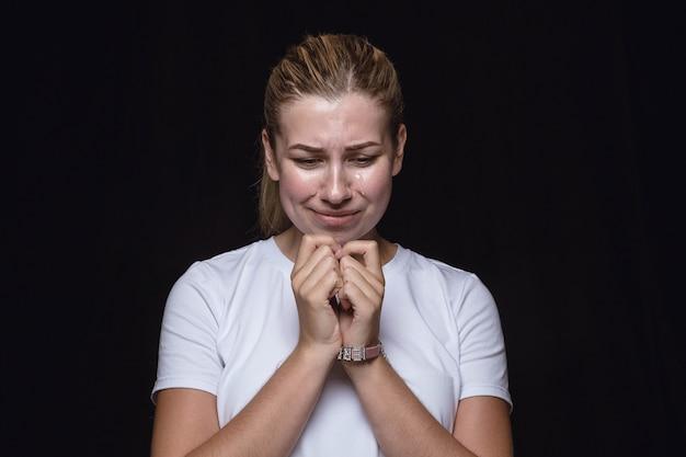 Ciérrese encima del retrato de la mujer joven aislada en el espacio negro. photoshot de emociones reales de modelo femenino. llorando, triste, triste y sin esperanza
